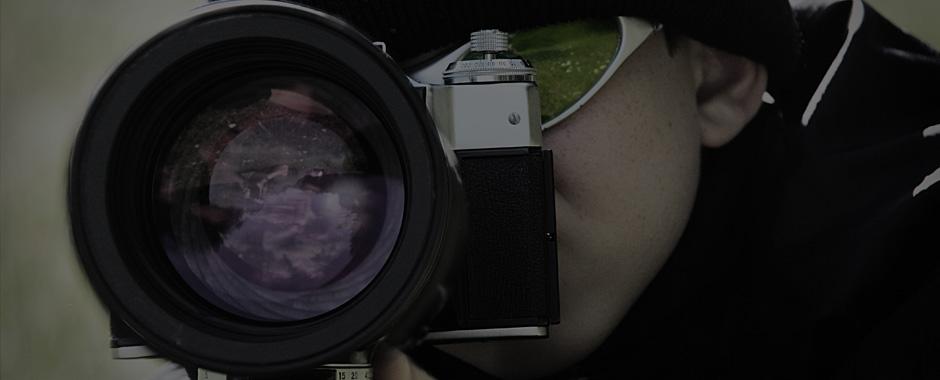 Espia sacando una fotografía con una cámara y un objetivo de larga distancia